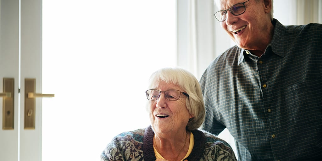 An elderly couple cheerfully receives a gift.